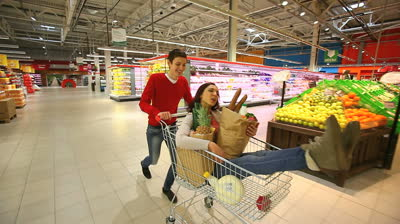 1358116040stock-footage-shoppers-having-fun-riding-through-the-mall-in-a-shopping-cart-full-of-groceries