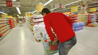 stock-footage-cheerful-young-man-having-fun-in-supermarket-swinging-the-cart-with-products